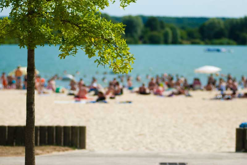 People sitting on sand at the edge of a clear water lake in the Loir Valley