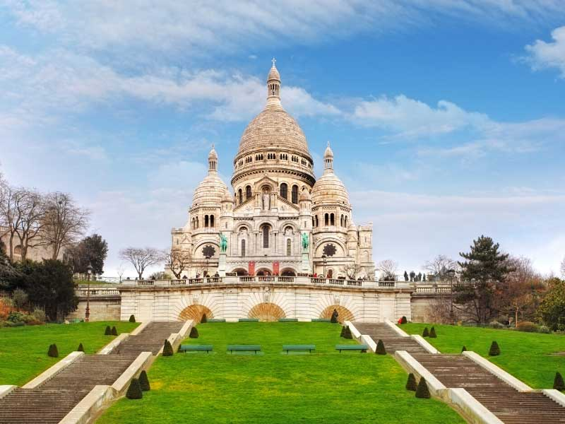 View of Sacre Coeur Church at the top of a hill, seen from the bottom of the hill, steps leading up