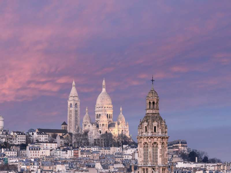 White stone domes of Sacre-Coeur Basilica in Paris standing out against a dusky sky