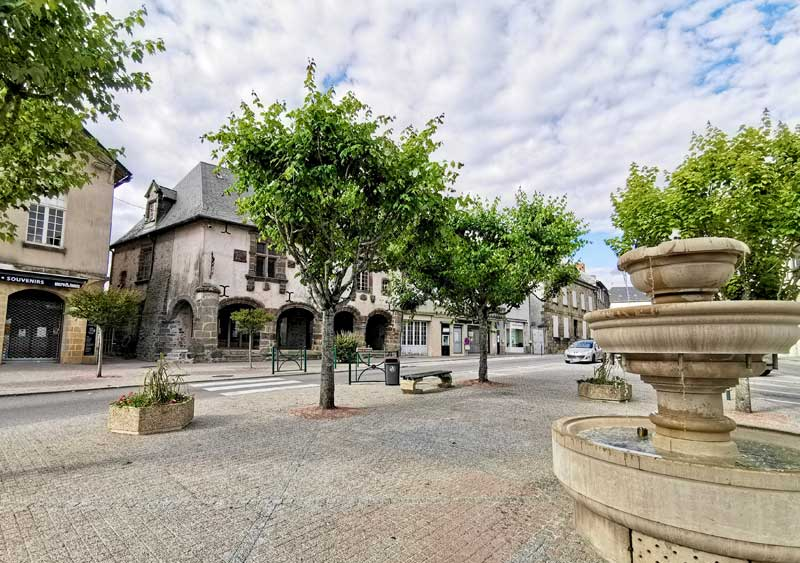 Pretty cobbled town square with fountains and trees in Lubersac, France