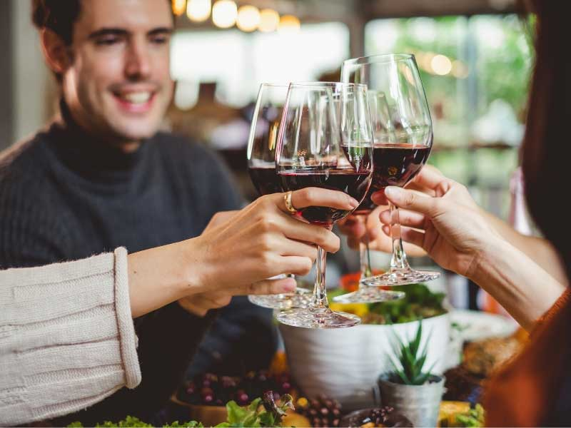 People clinking glasses of red wine together round a table laid for dinner