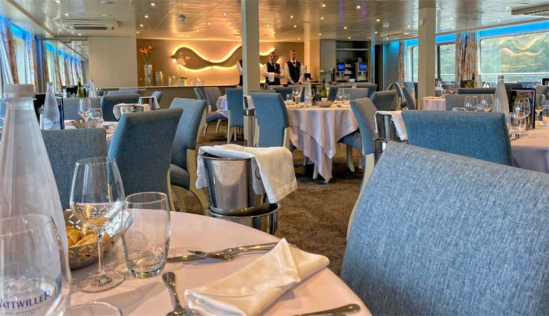 Large, spacious dining room on board Croisieurope ship with linen tablecloths