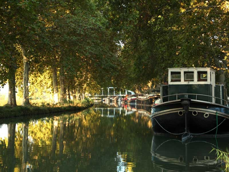 Barge tied up under trees that shade the Canal du Midi, France