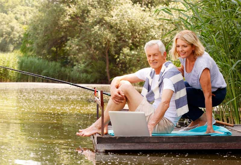 Man and woman fishing from a pontoon and using a tablet to check emails
