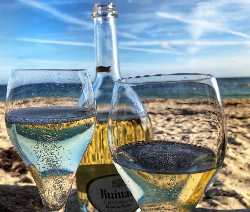 Two glasses and a bottle of Champagne on an empty sandy beach, Morbihan, Brittany