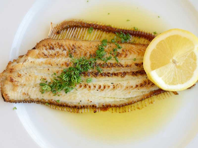 Fish on a plate, drizzled with butter and parsley and a lemon wedge