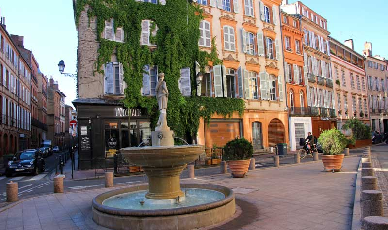 Pretty, red brick building lined square in Toulouse with a fountain in the centre
