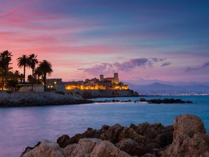 Coastline of Antibes at night, twinkling city under a dusky sunset