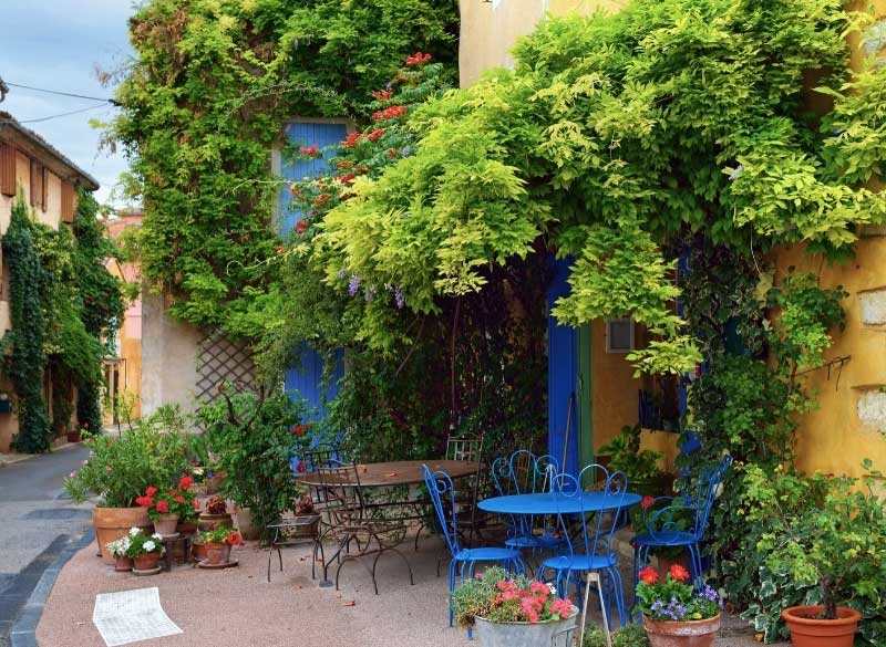 Street in Antibes, flowers and plants clambering over walls, tables and chairs on the pavement