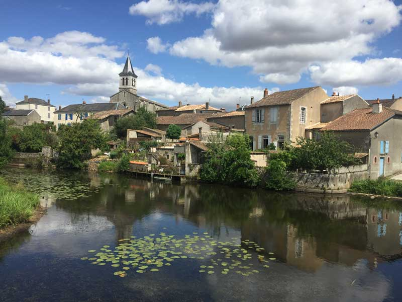 Pretty riverside town with a church and ancient houses in Sanxay, Deux-Sevres
