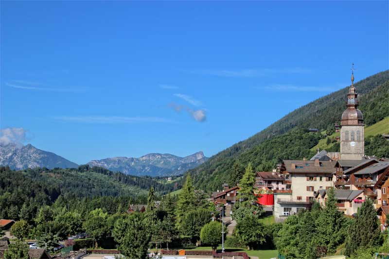 Mountain village under a sunny sky, snow peaked mountains in the background, Annecy Mountains