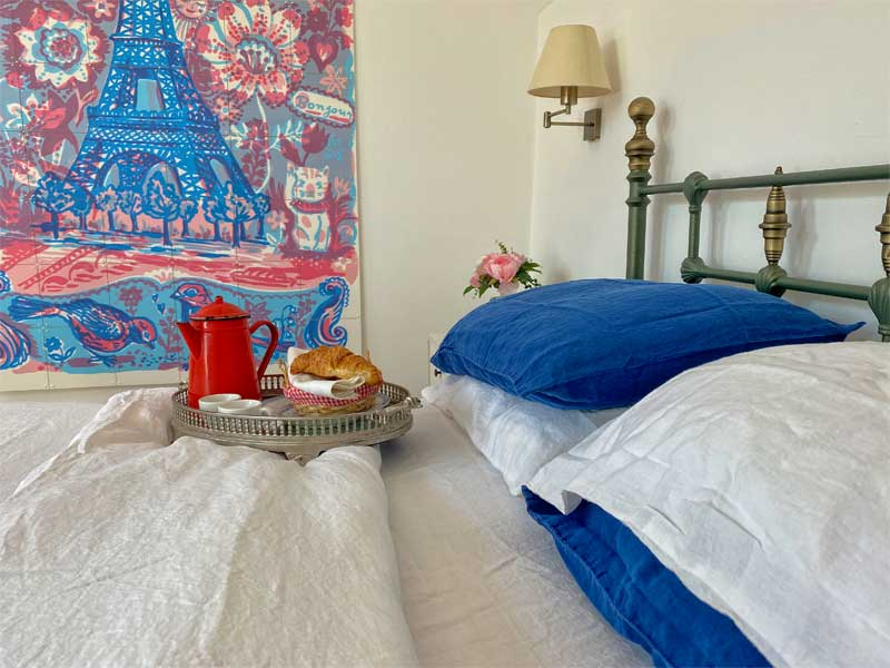 Tray on a bed with coffee and croissants, a picture of the Eiffel Tower and blue and white bedding