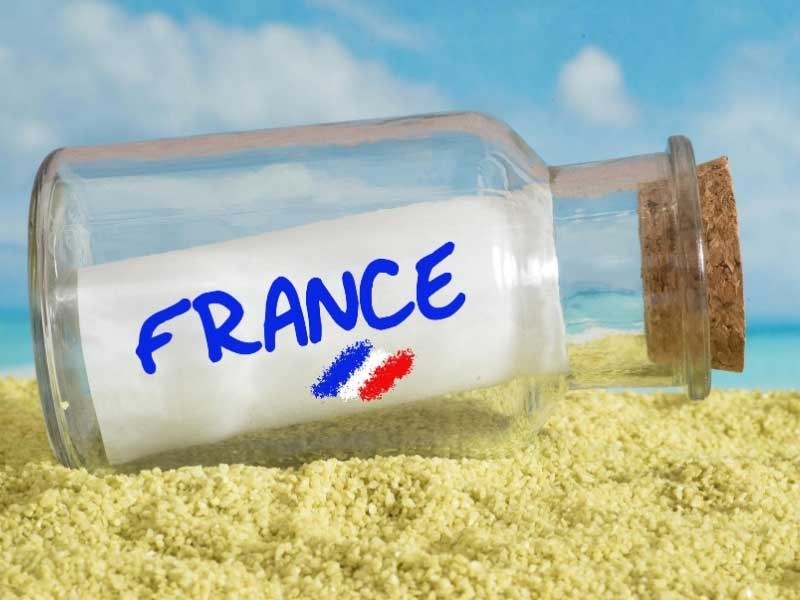 Glass bottle with a piece of paper saying France, on a sandy beach
