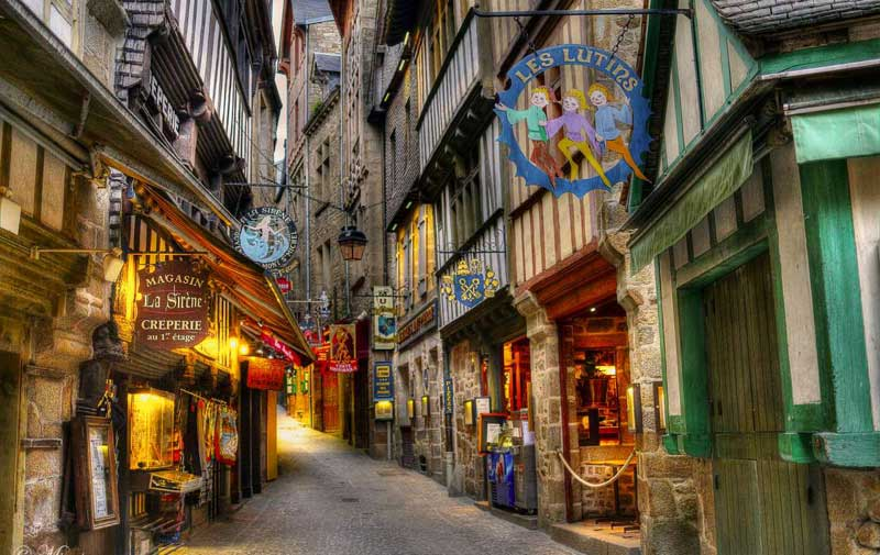Cobbled street lined with quaint shops in ancient buildings on island of Mont Saint-Michel