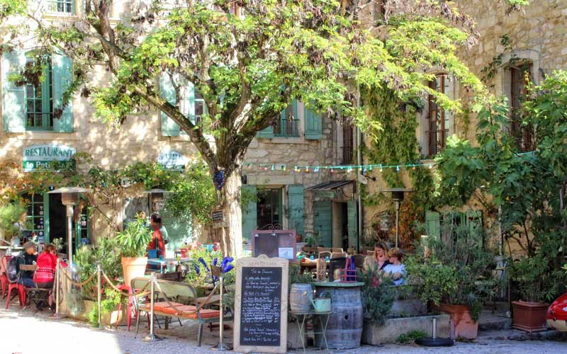 Pretty cafe in a village in Provence, leafy terrace with tables outside on the terrace