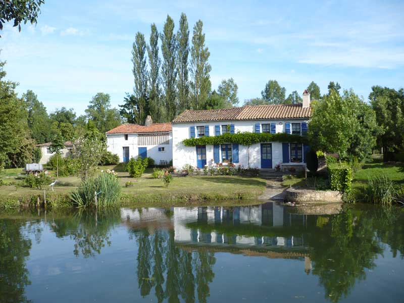 House alongside a river, typical of the Charente area, white washed walls and blue shutters