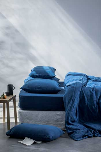 Plump pillows on a bed with blue sheets in a minimalist bedroom