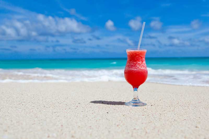 Bright red cocktail on a white sandy beach against a sunny sky and gentle sea lapping the beach