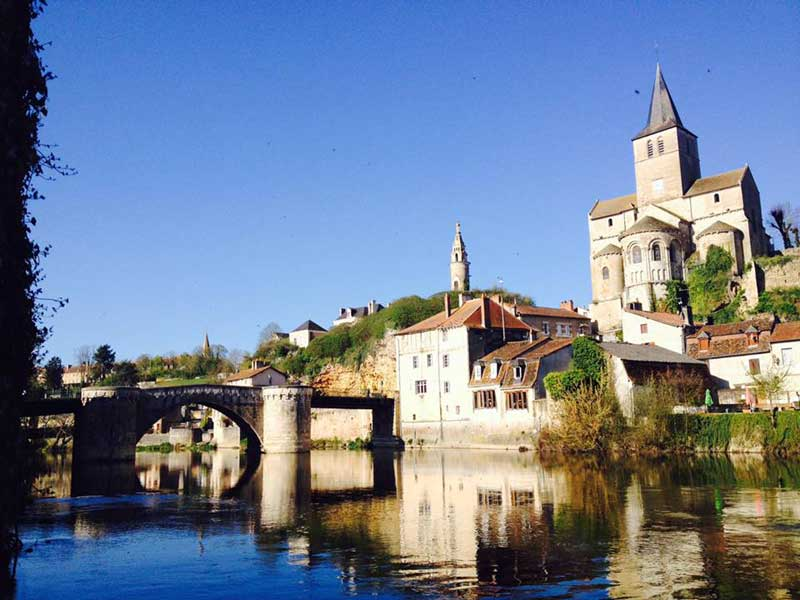 View of the town of Montmorillon across a river, church steeples and ancient buildings...