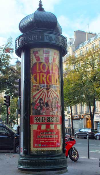 Tall, green advertising column, Morris Column, with a poster for Folies Bergeres