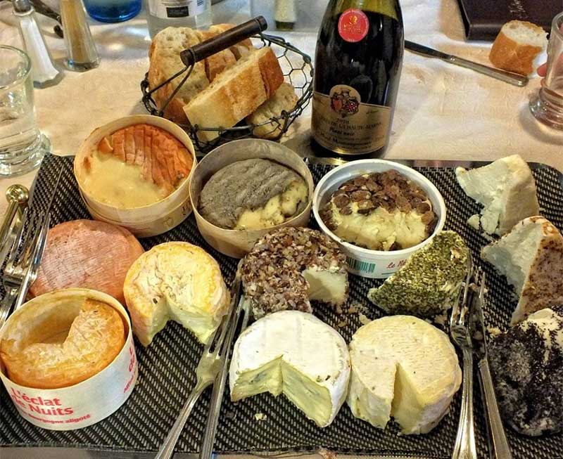 Cheese tray laden with French cheeses on a table with a bottle of wine and basket of bread
