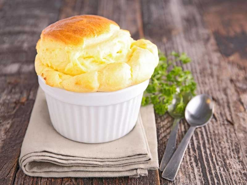 A cheese souffle risen to perfection in a china bowl, sprig of parsley to decorate
