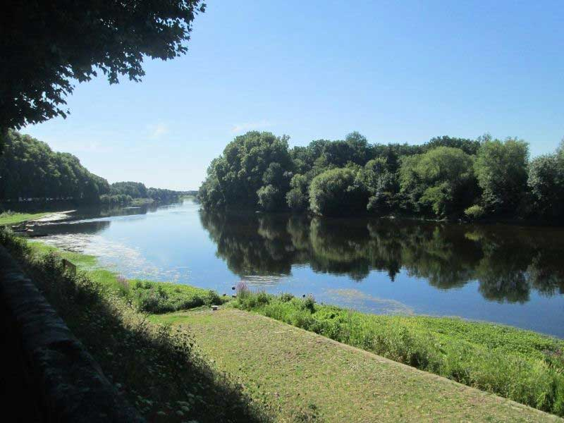 River runs through tranquil countryside, edged by forests in the Vienne deparment