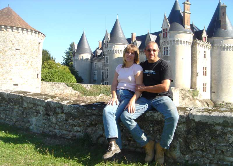 Man and woman sit on a castle wall in the Vienne department, France