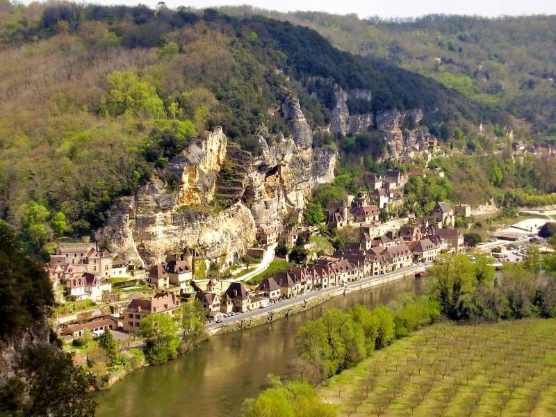 Village carved into rocks alongside the River Dordogne, France