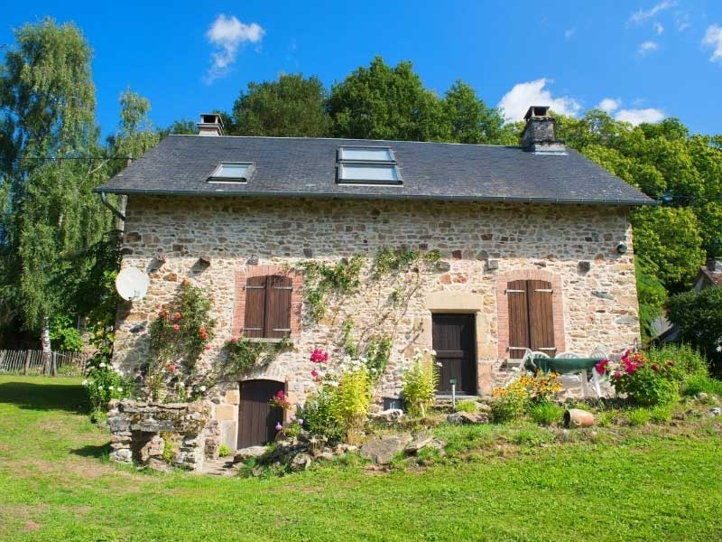 Rustic French house with wooden shutters and roses growing up the wall