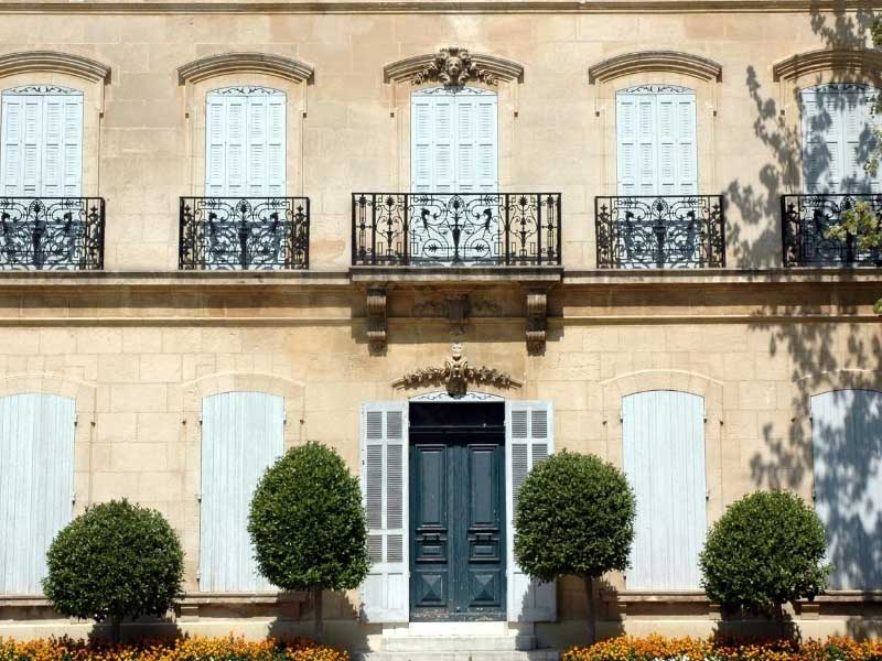 Stone house with tall windows with iron railings and white shutters - dream French house