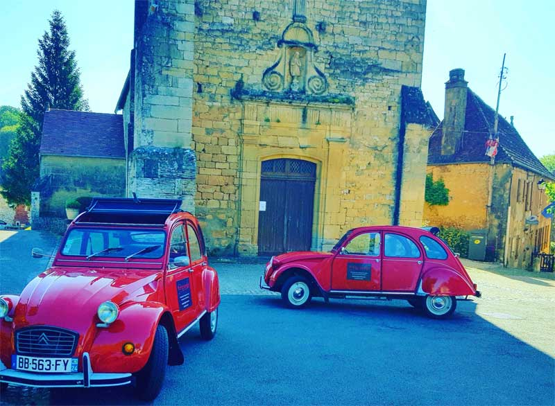 Cherry red 2CV cars lined up to take passengers on a tour