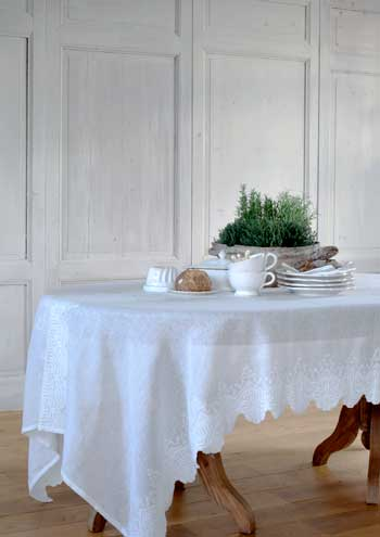 Table covered in a white cloth, white tea cups and plates stacked next to a green plant