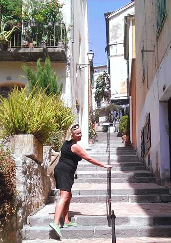 Woman climbs cobbled steps in town of Villefranche-sur-Mer