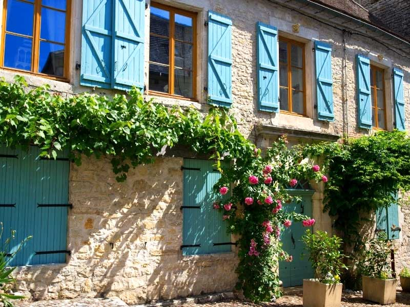 House with blue shutters and roses growing over the door typical French house style