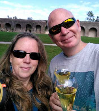 Man and woman hold up glasses of sparkling wine, smiling
