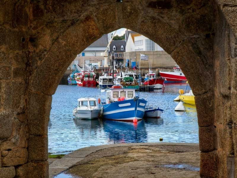 View though a stone arch to a port filled with colourful little fishing boats in Concarneau, Brittany