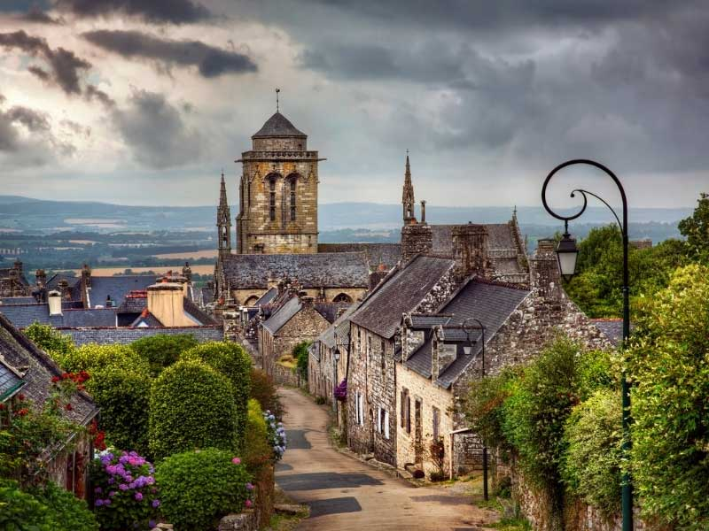 Ancient houses line a narrow cobbled street at the end of which a church tower looms in Locronan, Brittany