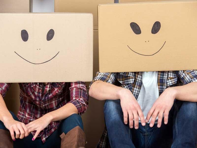 Couple avec des cartons vides sur la tête, décorés de visages souriants!