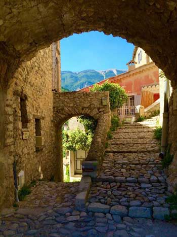 Cobbled street runs under a stone archway along a street lined with stone houses, Brantes, Provence