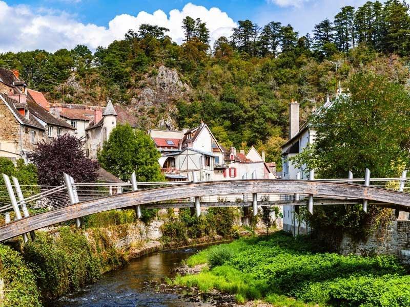 Narrow footbridge over a gentle stream in Aubusson, Creuse, France