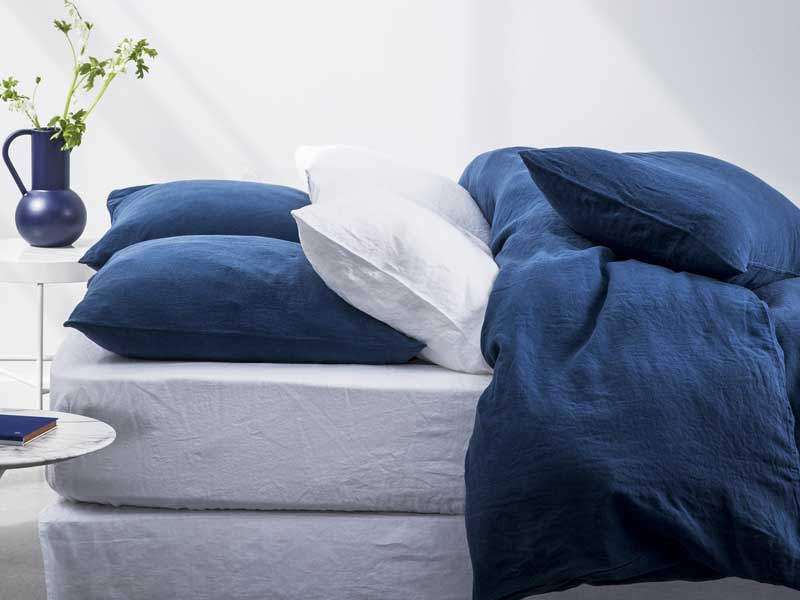 Bed made up with white and blue bed linen against a white background