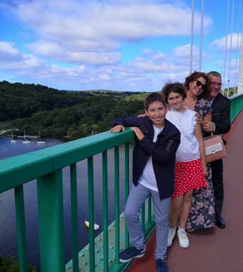Man, woman and two kid standing on a bridge enjoying the sights in Brittany