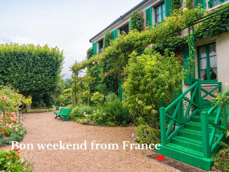 Courtyard in front of Claude Monet's house in Giverny, Normandy, surrounded by blooms and vines