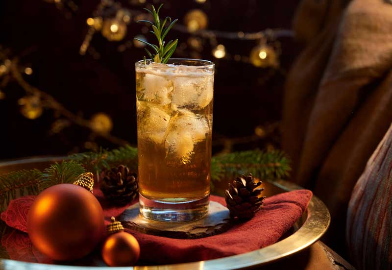 Glass of brandy with ginger ale and a sprig of rosemary and ice