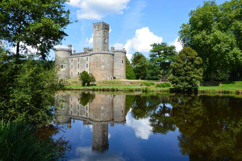 Castle with a tall square tower alongside a river, Chateau de Chalus in Limousin