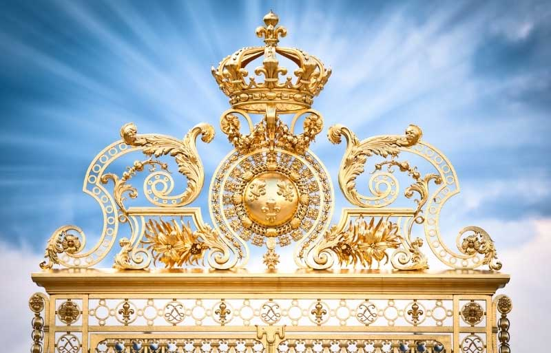 Ornate golden gate at the Chateau of Versailles against a deep blue sky