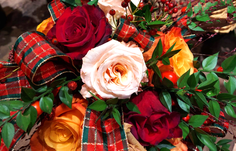 Bouquet of flowers, red and orange roses, berries and leaves tied with tartan ribbon