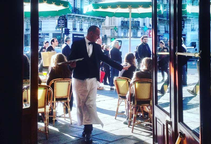 Waiter in a cafe in Paris takes an order for coffee from a seated client