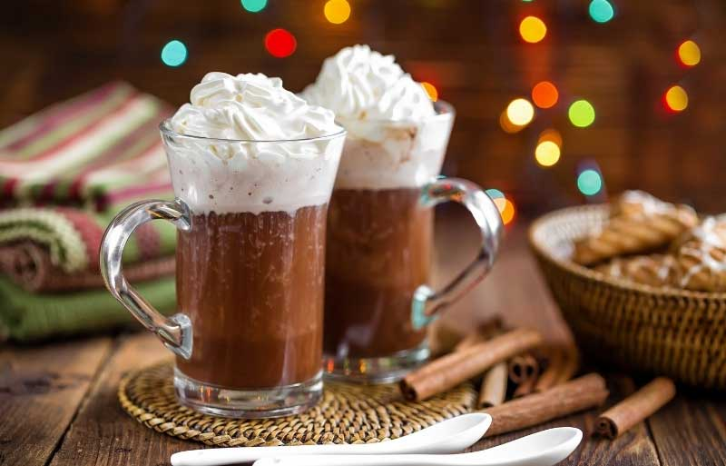 Two glass cups of hot chocolate with cream on top